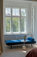 Blue couch in patch of sunlight in window bay in classic bedroom