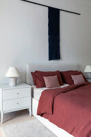 White bed with red bed linen and wall hanging in bedroom