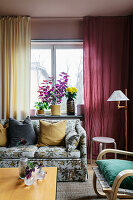 An upholstered sofa with a floral pattern in front of colourful curtains in a living room