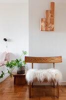 An animal fur on a wooden chair against a wall in a bedroom