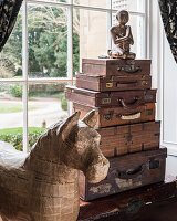 Filipino papier mache horse next to collection of vintage travel and writing cases