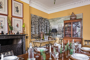Framed hand painted warriors hang above a marble mantlepiece in dining room with 18th century french dining table and hand painted french chairs