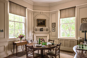 Wooden dining table and chairs in cream panelled room