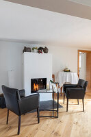 Leather armchairs and glass table in front of fireplace in bright room