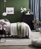 Doppelbett und Kommode mit üppigem Blumenstrauß vor grüner Wand