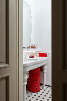 Vintage washbasin, above it red cabinet in the bathroom