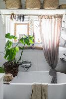 Free-standing bathtub with houseplant