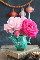 Pale and deep pink roses in bird-shaped vase