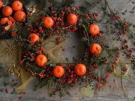 Wreath of cotoneaster berries, rose hips, spruce branches and tangerines