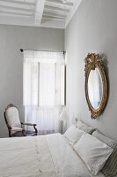 Gold frame mirror above double bed in bedroom with light grey walls