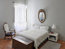 Gold-framed mirror above double bed and chest in bedroom with light grey walls