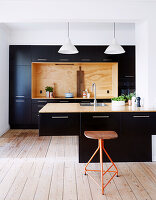Contemporary kitchen with black cupboard fronts and counter