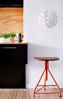 Vintage stool below pendant lamp next to counter