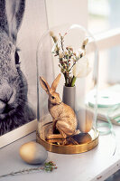Gold-coloured Easter bunny and posy of flowers under glass cover