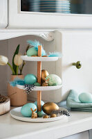 Blue and gold Easter eggs on cake stand