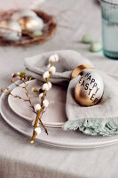 Gold-coloured Easter egg with 'Happy Easter' motto decorating plate