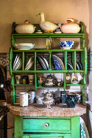 Old green painted plate rack in rustic kitchen