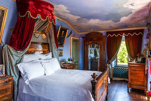 Antique double bed in blue painted bedroom with ceiling painting