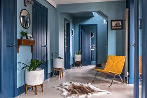 Gelber Polsterstuhl im Flur in Blau mit Zimmerpflanzen in einer Reihe