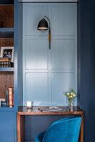 Schreibtisch an graublauer Kassettenwand mit Wandleuchte