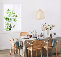 Gedeckter Tisch mit Leinentischdecke und Klassikerstühlen