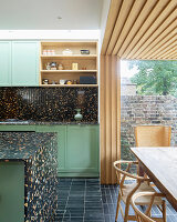 Open-plan kitchen with black terrazzo elements and dining area in extension