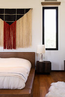 Fringed wall hanging above leather-upholstered bed