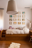Gallery of pictures on wall above bed in child's bedroom decorated in shades of brown