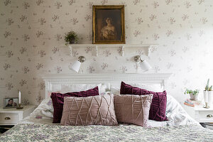 Double bed in the bedroom with romantic wallpaper