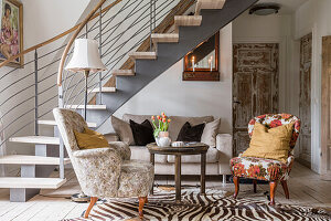 Upholstered furniture on zebra skin in the living room with staircase