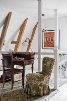 Small antique desk with chair and armchair with romantic cover on stair landing