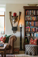 Leather couch next to antique bookcase, candlestick and animal head