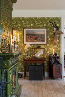 Tiled stove and antiques in room with green wallpaper