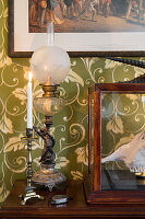 Antique table lamp and candlestick on wooden table in front of green wallpaper