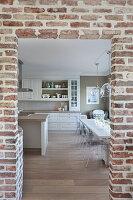 Blick durch Backstein-Durchgang in die Küche mit langem Esstisch und transparenten Stühlen