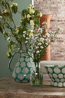 Blumen und Hartriegelzweige in grünem Krug und einer Glasvase