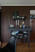 Shelf and console with dishes in front of dark wall in kitchen