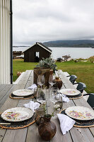 Covered wooden table with chairs on the terrace with a view of the Lofoten Islands