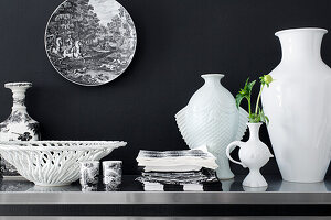 Vases, bowls and tableware in white in front of a black wall