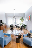 Light blue designer armchair with side table, retro sideboard and dining area