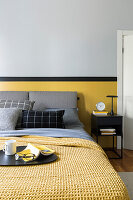 Double bed with grey bed headboard and yellow bedspread