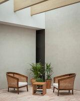Minimalistische Sitzecke mit Backsteinboden vor grauer Wand