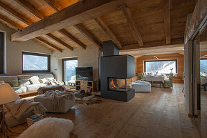 Offener Wohnraum mit gemütlichen Sitzmöblen, Dielenboden, Kaminofen und Holzdecke