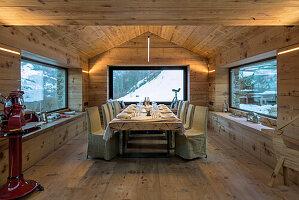 Langer, gedeckter Tisch mit Hussenstühlen im Esszimmer mit Holzverkleidung