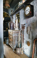 Old pendulum cock, chest of drawers and junk in hallway with battered walls
