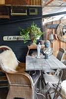 Wicker chair with sheepskin rug at wooden table on terrace with vintage-style accessories
