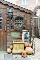 Wreath, planter and terracotta balls outside garden shed