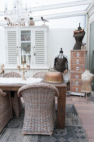 Wicker chairs around dining table in shabby-chic conservatory