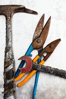 Hammer, tin snips and wrench on metal surface