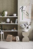 Weiße Regale mit Dekoobjekten, Moderne Kunst an der Wand, davor Betonhocker mit Blumenstrauß